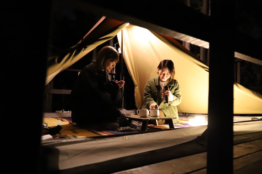 テントの中で赤ワインを飲む女性